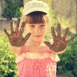 女孩显示她肮脏的手 被定调子的图象 免版税图库摄影