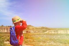 有远足在山的双筒望远镜的小男孩 免版税库存照片