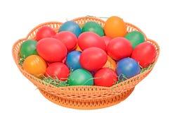 在一个棕色篮子的色的复活节罗马尼亚传统鸡蛋,关闭,被隔绝的,白色背景 免版税库存照片