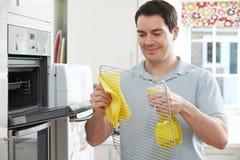 清洗国内烤箱的人在厨房里 图库摄影