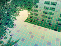 抽象反射大厦在五颜六色的游泳池的水中 免版税库存照片