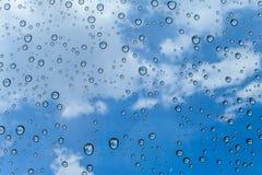 雨水滴在玻璃和蓝天背景/下落的在玻璃 免版税库存图片
