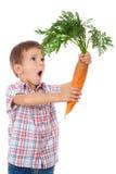 惊奇男孩用大红萝卜 免版税库存图片