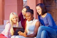 交往通过片剂的互联网的美丽的多种族女性朋友 免版税库存照片
