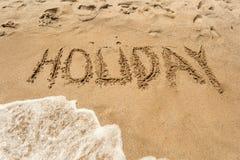 在海滨的湿沙子写的假日 免版税库存图片