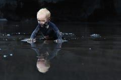 爬行在湿黑沙子海滩的肮脏的孩子 免版税库存照片