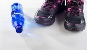 Идущие ботинки и бутылка воды на белизне Стоковые Фотографии RF