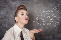 美丽的妇女送图画心脏 免版税库存照片