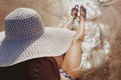 有帽子的妇女在热带手段的游泳池附近 库存图片