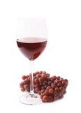 Ποτήρι του κόκκινου κρασιού δίπλα σε έναν κλάδο των σταφυλιών Στοκ εικόνα με δικαίωμα ελεύθερης χρήσης