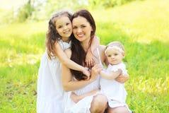 愉快的年轻家庭、母亲和两个女儿孩子的一起 库存照片