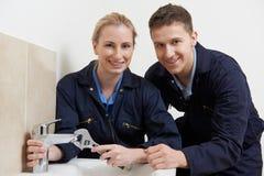 女性实习生水管工工作可随时使用在卫生间里 免版税库存照片