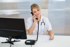 年轻女性医生谈话在电话 库存照片