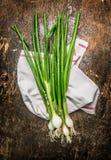 在黑暗的土气木背景的葱束 免版税图库摄影
