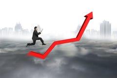 拿着片剂的商人跳跃在红色成长倾向线 免版税库存照片