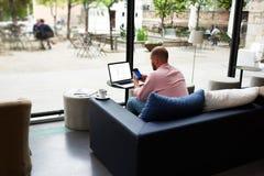 现代商人繁忙研究巧妙的电话和便携式计算机 免版税库存照片