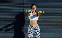 拿着重量用手的运动的妇女在她的得到在了不起的形状的前面胳膊 库存图片