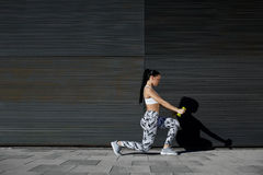 Атлетические женские поднимаясь весы пока разрабатывающ против стены с космосом экземпляра для вашего текстового сообщения Стоковая Фотография