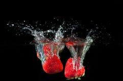 飞溅到水的草莓 免版税库存照片