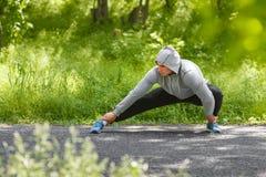 Молодой атлетический человек делая протягивающ тренировки, внешние Здоровый человек разрабатывая в парке Стоковые Фотографии RF