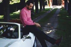 拿着司机或高尔夫俱乐部的英俊的高尔夫球运动员,当准备好在路线时的一天 免版税图库摄影