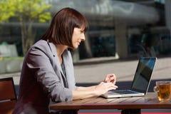 使用膝上型计算机的女商人在咖啡馆在断裂期间 免版税图库摄影