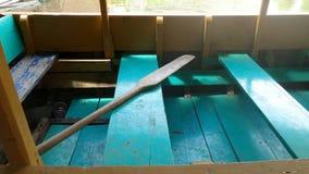 五颜六色的木位子和桨在小船运送 免版税库存照片