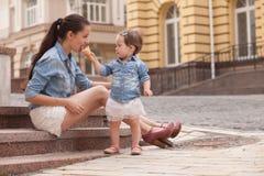 女孩和母亲获得与冰淇凌的乐趣 免版税库存图片