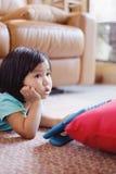 女婴观看的电视,当拿着片剂时 免版税库存图片
