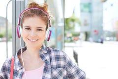 愉快的妇女佩带的耳机画象,当等待在公共汽车站时 库存照片