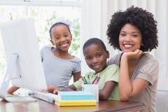 使用计算机的愉快的家庭 免版税库存照片