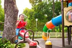 愉快的孩子,男孩获得在操场的乐趣在公园 免版税库存照片