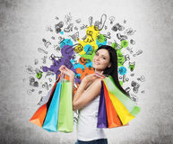 有五颜六色的购物袋的美丽的微笑的少妇从花梢商店 免版税库存图片