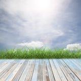 与美好的蓝天风景的木地板背景的 库存图片