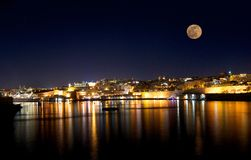 美丽的瓦莱塔在与满月的晚上在与星的蓝色黑暗的天空背景中 免版税库存图片