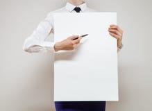 拿着一张白色海报的无法认出的年轻女实业家 库存照片