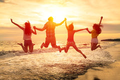 счастливое молодые люди скача на пляж Стоковые Фотографии RF