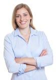 蓝色女衬衫的美丽的白肤金发的德国妇女有横渡的胳膊的 免版税图库摄影