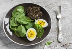 健康快餐-新鲜的菠菜和一个鸡蛋在一块棕色板材 库存图片