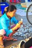 越南妇女在一个地方海鲜市场上卖她的鱼 免版税库存图片