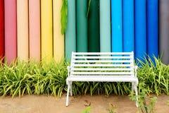 白色铁长凳和多色具体篱芭 免版税库存图片