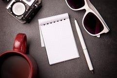 笔记薄、玻璃、笔和杯子在桌上 免版税库存照片