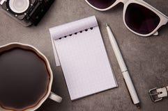 笔记薄、太阳镜、笔和杯子在桌上 免版税库存图片