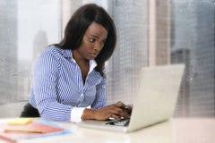 坐在商业区办公计算机膝上型计算机书桌键入的年轻可爱和高效率的黑人种族妇女 图库摄影