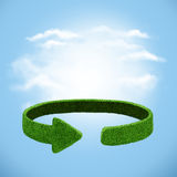 从草的绿色箭头在天空背景 回收概念 免版税库存照片