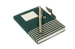 在方格的布料盖子的笔记薄有夹子和笔的 库存照片