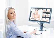 工作在办公室的年轻,可爱和确信的妇女 免版税图库摄影