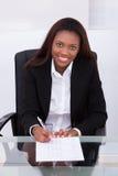确信的在书桌的女实业家填装的形式在办公室 库存图片