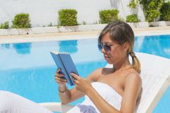 读书的女孩,当晒日光浴由水池时 免版税库存照片