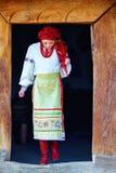 年轻乌克兰女孩,打扮在全国服装,走出去从房子 免版税库存图片
